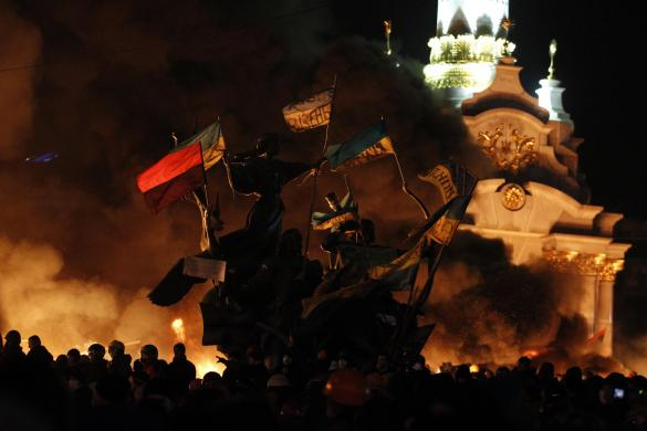 Anti-government protesters gather near a statue during clashes with riot police at Independence Square in Kiev